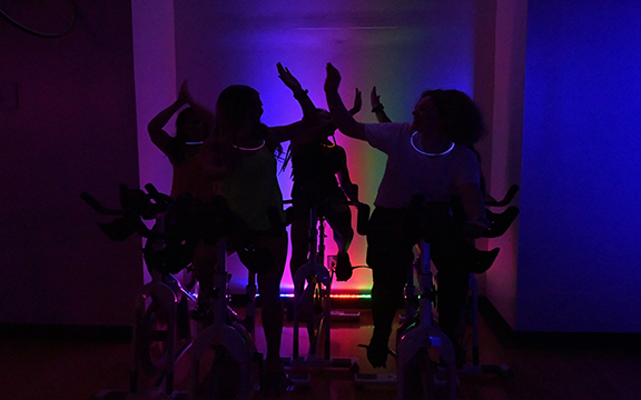 Participants in a glow in the dark fitness class
